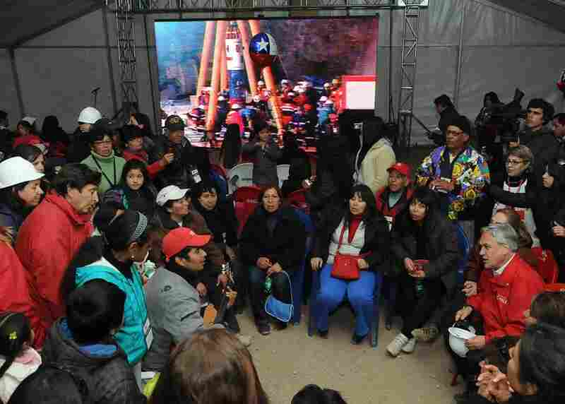 President Pinera (seated bottom right holding hard hat) meets with relatives of the trapped miners before rescue operations began Tuesday night.