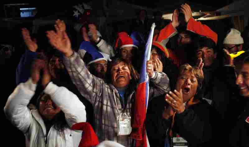 Relatives and friends celebrate while watching the rescue of Florencio Avalos on a television screen outside the mine.