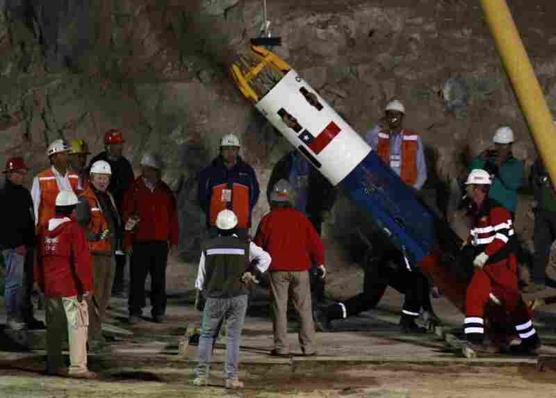Rescue workers and officials test the capsule that will be used to extract the miners.