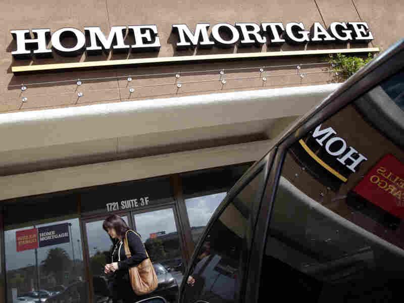 A woman walks past a Wells Fargo Home Mortgage office in La Habra, Calif.