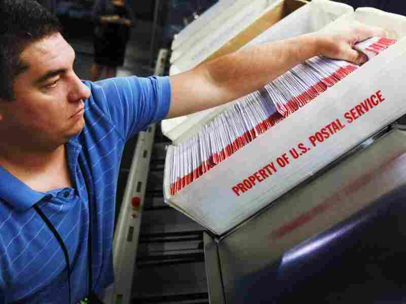 Julio Galligaris sorts through mail-in ballots that have been received in Doral, Fla.