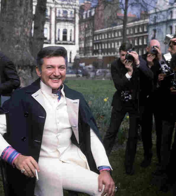Liberace holds the attention of a group of photographers in a London park.