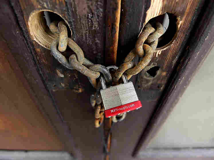 A chain and padlock take the place of door knobs and locks on a foreclosed home in the Bronx, N.Y.