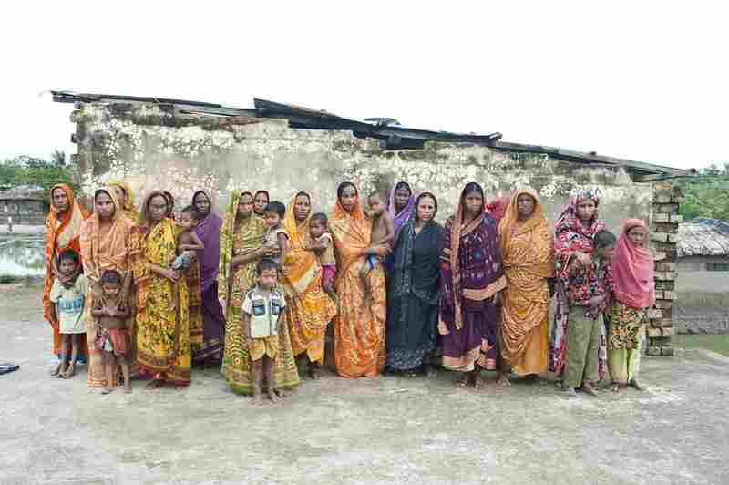 Eighteen widows of tiger victims pose for a portrait; the youngest is 22 years old. One woman lost her husband two months ago. They are part of a struggling self-help group run by an NGO.