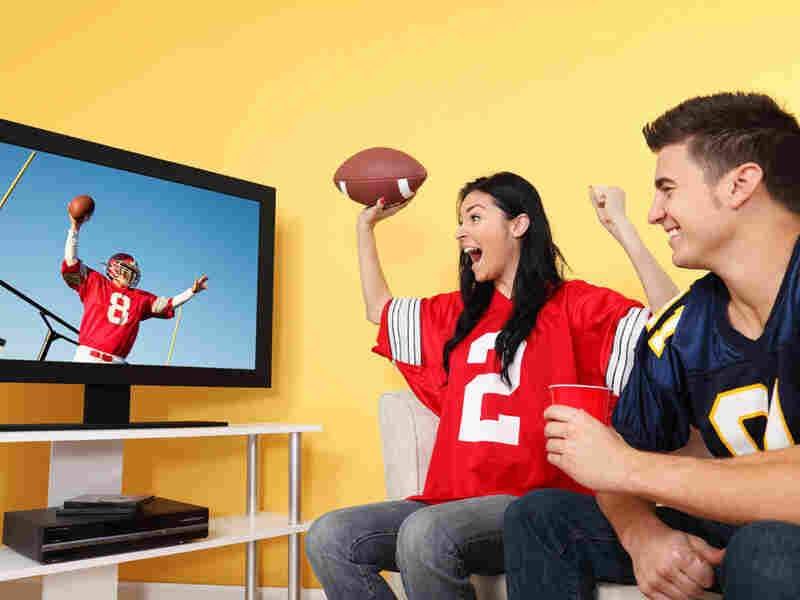 Fan watching football game yells at a touchdown.