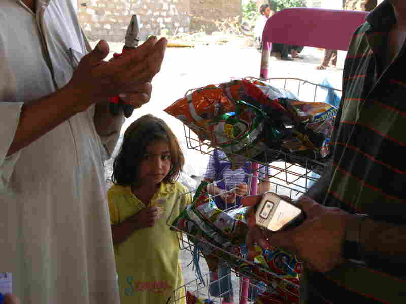 A young girl waits to buy snacks from an Arab man.
