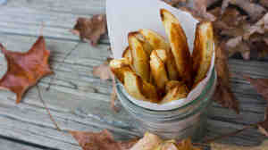 Oven fries are gathered in a glass jar with paper liner and placed among fall leaves.