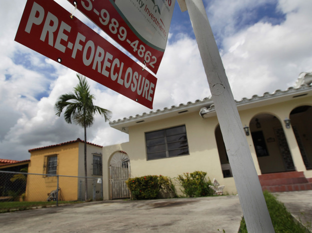 A pre-foreclosure sign hangs in front of a home in Miami.
