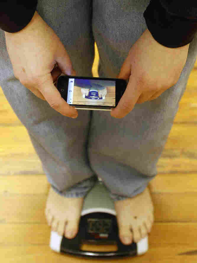 person using phone to track weight