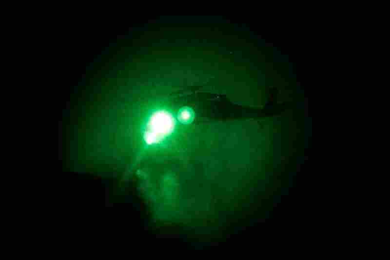 An Army Black Hawk helicopter is seen through a night vision lens as Alpha Company attempts to guide it to a landing near the disabled helicopter. The landing zone is too small, and the men must jump from their hovering chopper. By the time they reach the landing zone, the small-arms fire has ceased and they head down a steep mountain to safety.