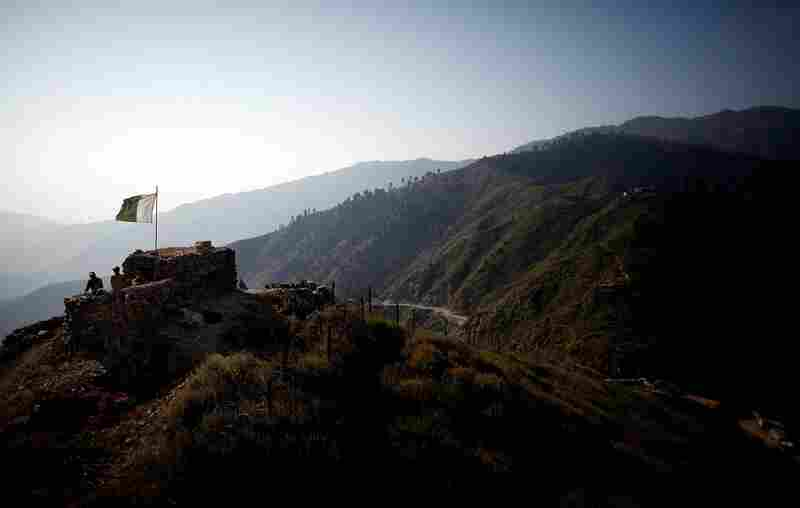 The Pakistani flag waves on the Afghan border at the Ghakhi Pass in Afghanistan's eastern Kunar province. The volatile border, marked by a coil of razor wire, has been a source of constant friction as insurgents pass through the mountainous region.
