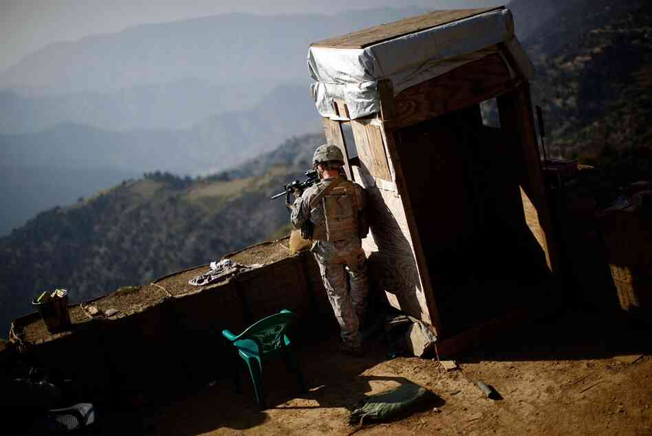 "A U.S. soldier keeps watch at a recently abandoned American base on the Afghanistan-Pakistan border. The soldiers refer to these compounds as belonging to the ""OGA,"" or ""Other Government Agency,"" common slang for the CIA."