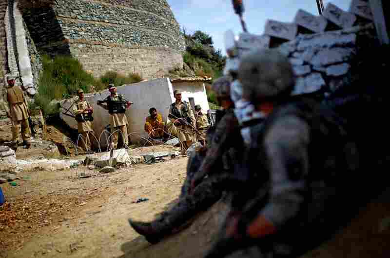 U.S. soldiers look over at members of Pakistan's paramilitary force as they stand guard at the Ghakhi Pass border. The U.S. soldiers have no way of knowing who might be associated with the Taliban.