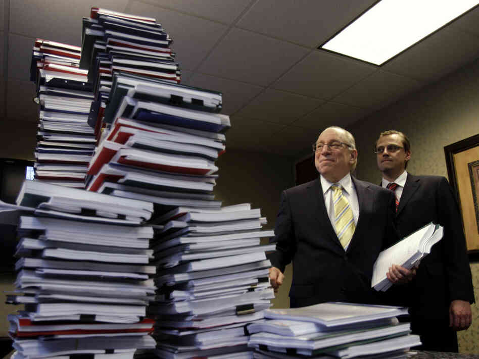 Attorneys pose with  stacks of depositions from 150 robo-signers.