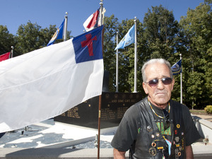 Air Force veteran Ray Martini guards a Christian flag