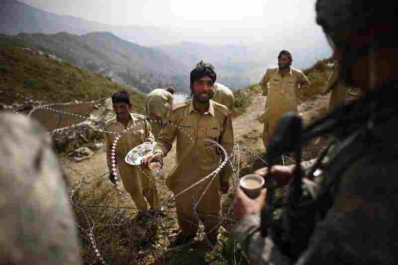 A member of Pakistan's paramilitary Frontier Corps passes tea to Lt. Kenneth Kovach through coils of wire separating Afghanistan and Pakistan. Elements of the Taliban and al-Qaida are believed to cross the border here from safe havens inside Pakistan.