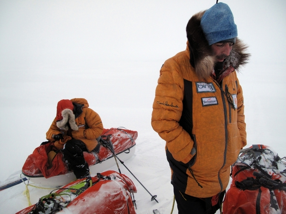 Antony Jinman (left) and Darcy St. Laurent, members of Larsen's team, huddle against the  blowing wind and cold during a short break on a trek in the Arctic on April 6.