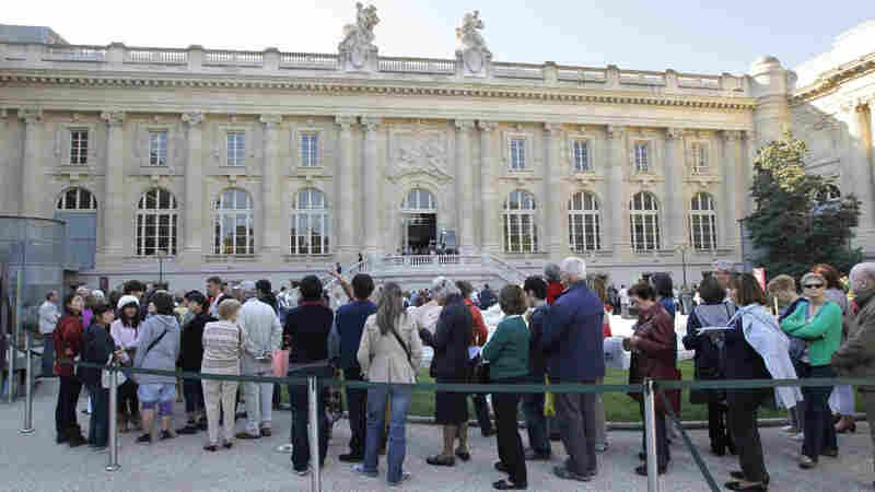 Visitors wait in line outside the Grand Palais museum in Paris.