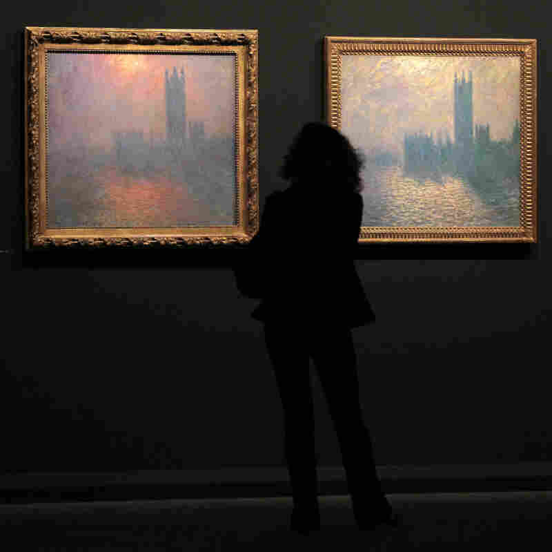 A woman looks at two paintings by Monet.
