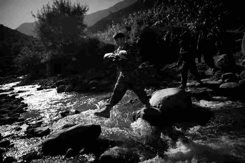 Near the border with Pakistan, an Afghan soldier crosses a river while on patrol in eastern Kunar province. Both the Afghan and American soldiers conduct these daily patrols looking for insurgents crossing into Afghanistan from Pakistan. October 2010