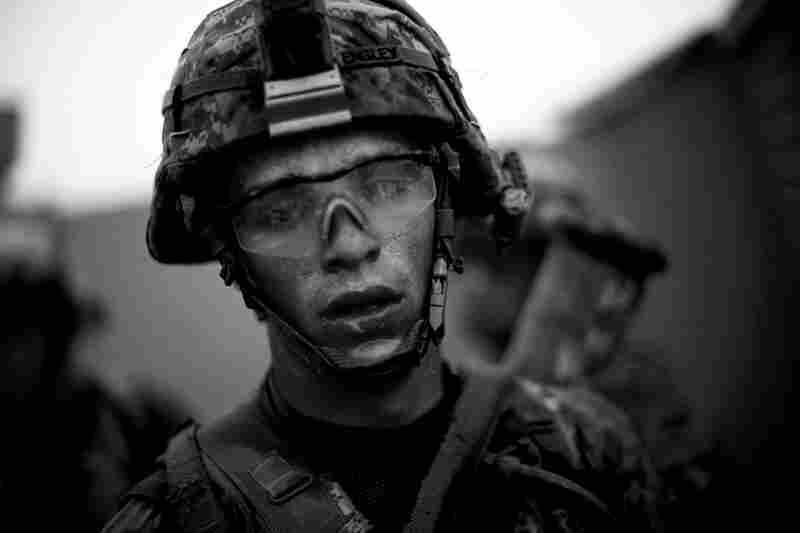 Bravo Company's Pvt. Cody Lee Ensley walks through the safety of the gates at an American base after a daylong fierce attack by insurgents near Payendi. July 2010