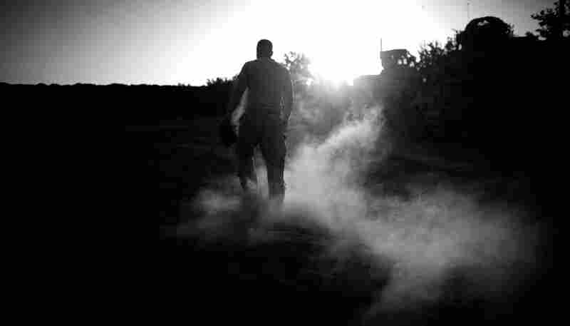 A U.S. soldier walks through the dust at Combat Outpost Stout while playing a game of baseball between patrols. October 2010
