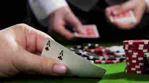A woman holds a pair of aces at a poker table.