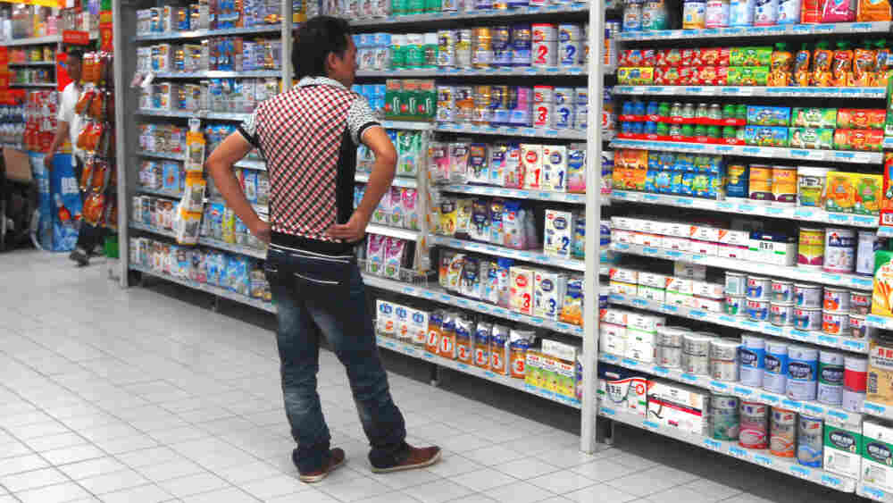 A man shops for milk powder at a supermarket in Guangzhou, south Guangdong Province