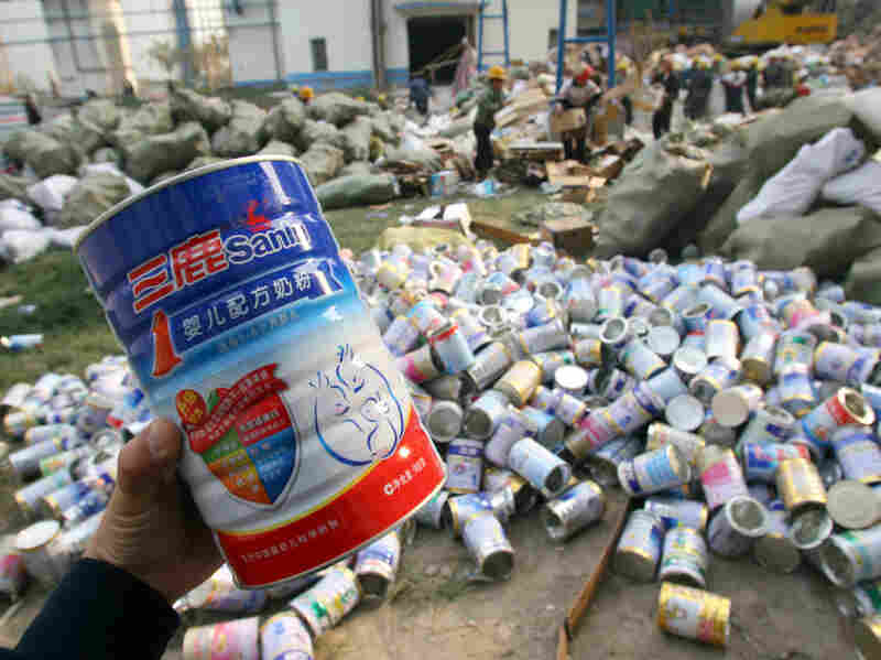 Workers pile up empty tins after contaminated Sanlu milk powder was poured into bags for destruction