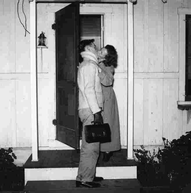 Cole Weston, son of photographer Edward Weston, kisses his wife, Dorothy, goodbye outside their home before heading off to work. At the time, Weston worked as a metalsmith at the Lockheed Aircraft Company plant in Burbank, earning 51 cents an hour.