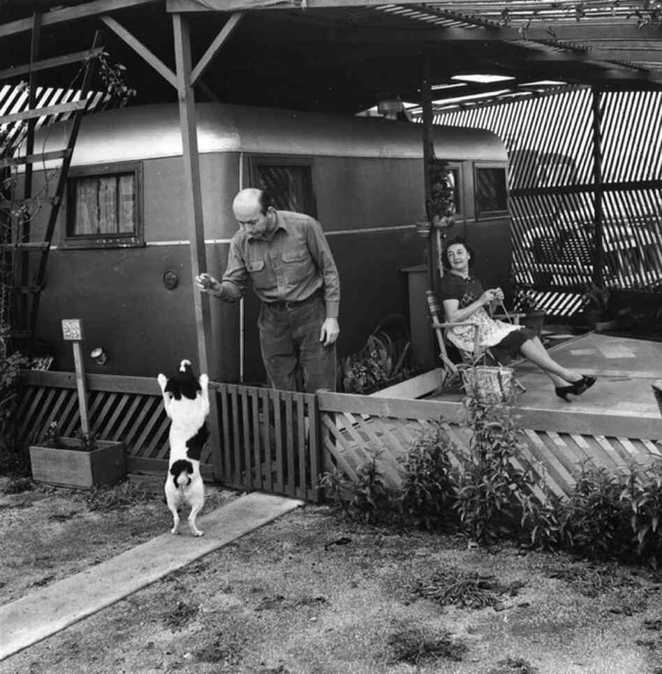 Residents of the Olympic Trailer Court in Santa Monica relax and play with their dog outside their trailer.