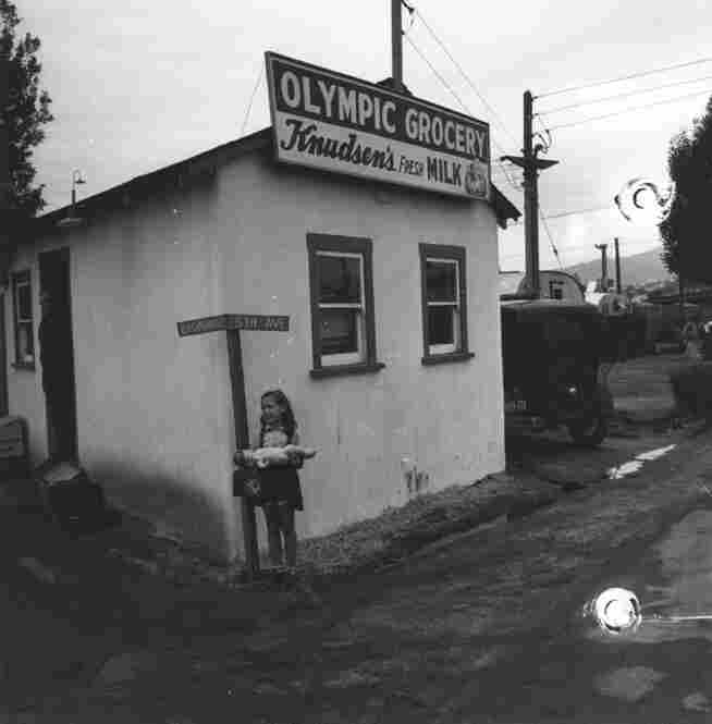 A young girl, seen with her baby doll, stands outside of Olympic Grocery in Santa Monica. Some residential trailers can be seen in the background on the right.