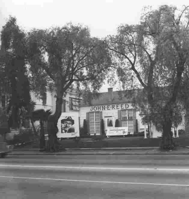 An exterior view of the photography studio owned by John E. Reed in Hollywood. On the lawn is a large photograph of entertainer Jimmy Durante.