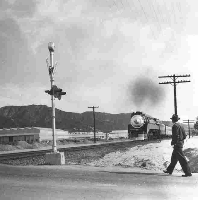 A man walks on an unidentified Burbank street. The Lockheed Aircraft plant and the Verdugo Mountains are seen in the background.