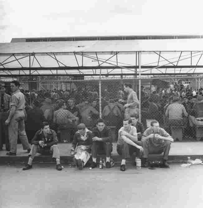 Hundreds of Burbank Lockheed Aircraft employees take a lunch break around a covered eating area.