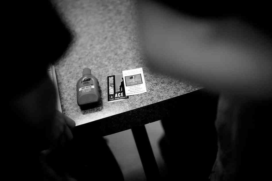 A bottle of hand sanitizer, a suicide prevention help card and an Army resource card on a table at the reception facility.