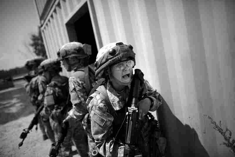 """Soldiers yell for help after """"enemy"""" fighters shoot at their patrol during a mock combat exercise. The Army has changed the way it trains new recruits. For the first time in 30 years, gone are the bayonets and long runs, replaced with  core exercises and sprints."""