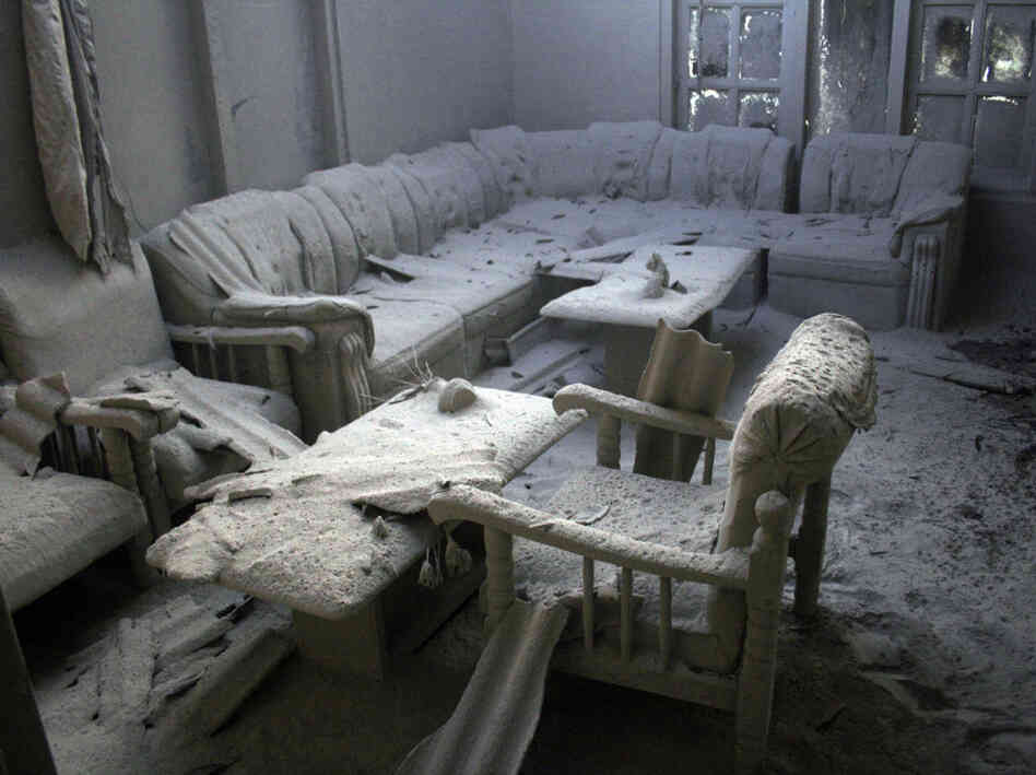 Furniture is covered by volcanic ash in a house in a village badly hit by