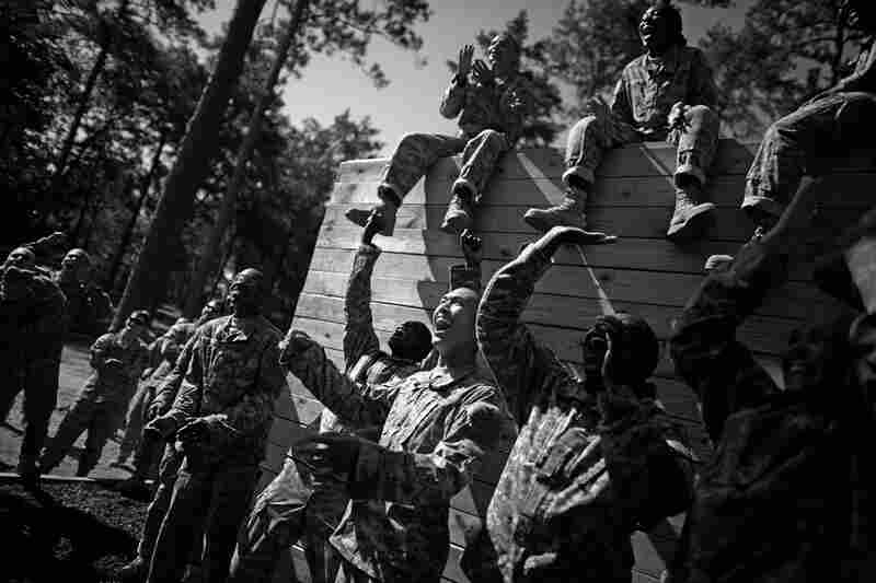 Soldiers cheer and jeer for private trying to make it over the highest wall on a climbing exercise and obstacle course.
