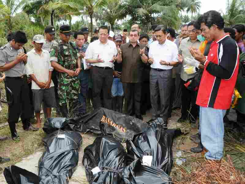 Indonesian officials pray over the bodies of tsunami victims on North Pagai island.
