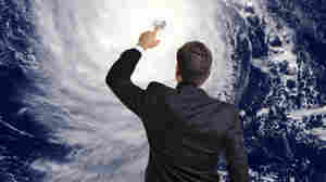 weatherman touching photo of hurricane