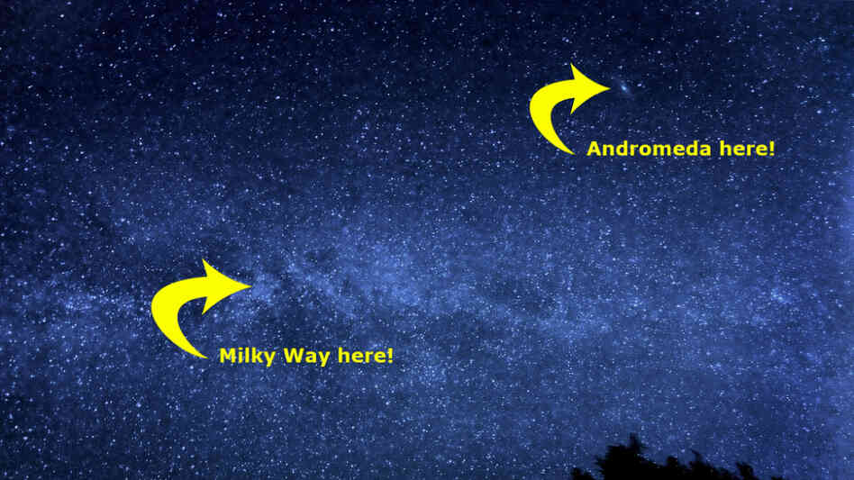 The Milky Way fills the night sky, and, if you look carefully, the Andromeda Galaxy is visible as th