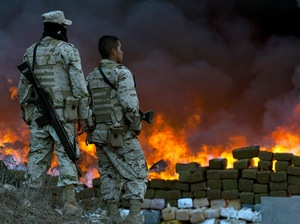 Two soldiers watch 134 tons of marijuana burning
