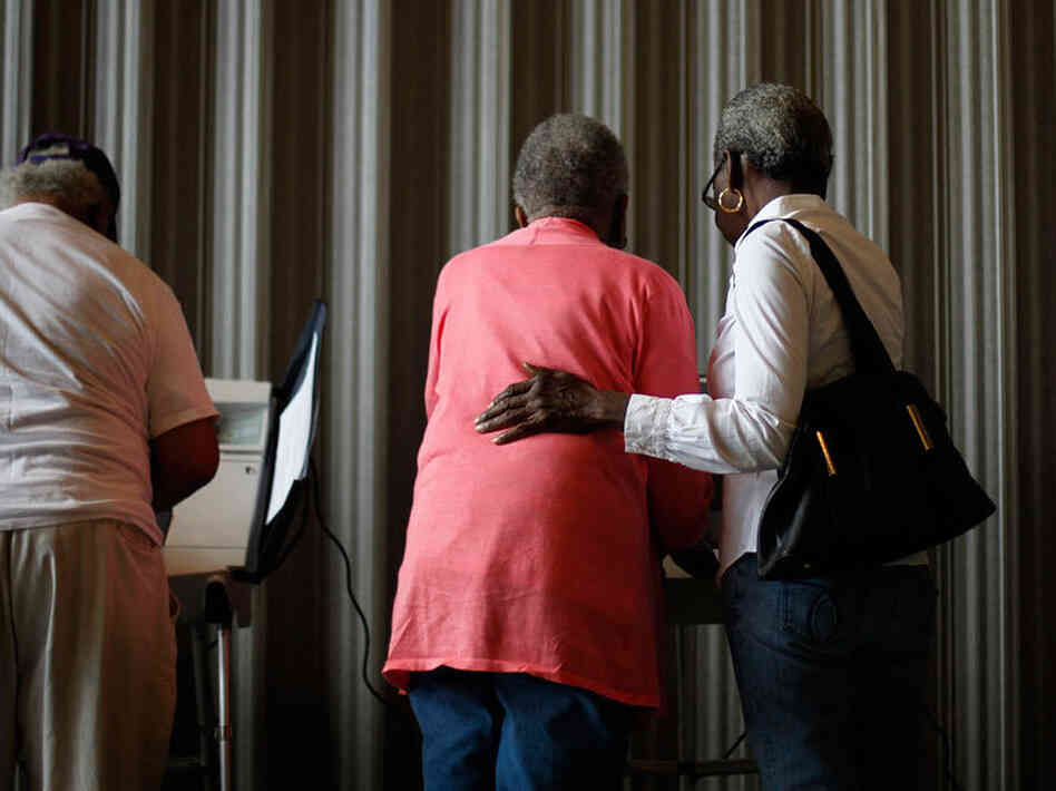 Marian Baker, 83, left, is assisted by Joann Lacy, 69, both of Atlanta, as she casts her ballot.