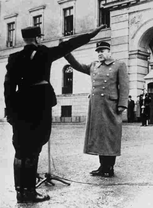 Norwegian traitor Vidkun Quisling (right) gives a Nazi salute following German occupation of the country. His name has come to mean traitor.