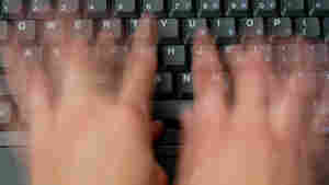 Fingers fly quickly over a computer keyboard.