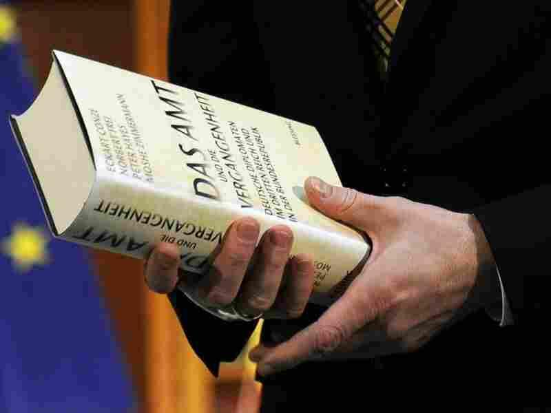"""German foreign minister Guido Westerwell holds the book """"Das Amt und die Vergangenheit""""."""