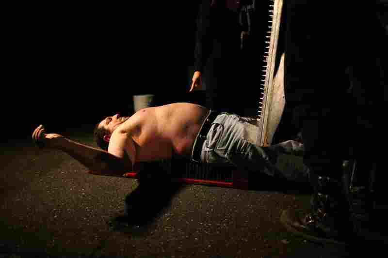 An entertainer prepares to have a board with nails pushed into his chest at the Pennhurst Asylum haunted tour.