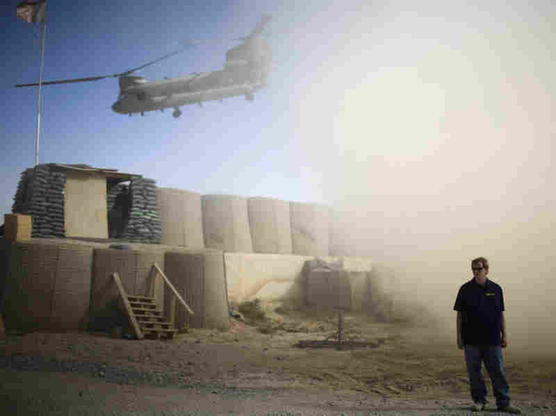 A U.S. contractor looks away from a dust cloud whipped up by a helicopter.
