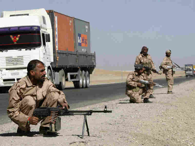 Private security contractors guard a part of a route as NATO supply trucks drive past.